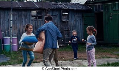 Happy kids fight pillows in yard of country house. Countryside. Entertainment.