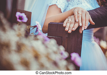 Bride and groom holding hands outdoors. close-up