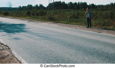 Man in sunglasses stay at road in countryside. Hitchhiking. Smoke cigarette.