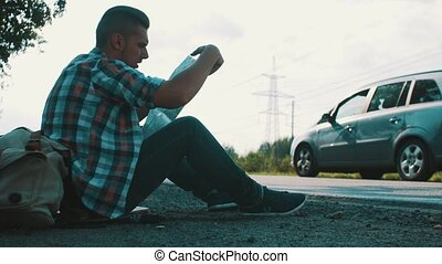Man sit at road in countryside with map in hands. Hitchhiking. Waiting.