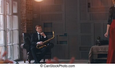 Jazz vocalist perform at microphone. Saxophonist sitting in chair. Retro style