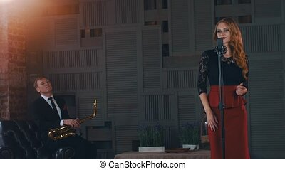 Jazz duet perform on stage. Saxophonist. Vocalist click fingers at microphone