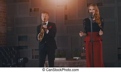 Jazz duet perform on stage. Saxophonist in suit. Singer in...