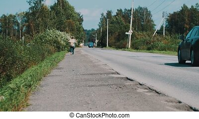Man walk along the road in countryside with cardboard plate. Hitchhiking. Travel