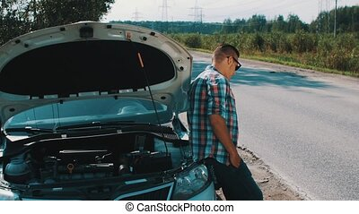 Man stand at car with opened capote at road in countryside....