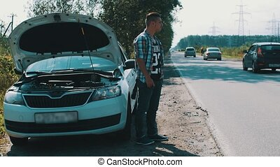 Man stay at car with opened capote at road in countryside....