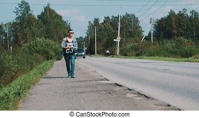 Man walk along the road in countryside with thumb up. Hitchhiking. Cars. Map.
