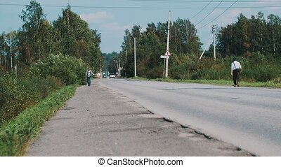 Man walk along the road in countryside with thumb up. Hitchhiking. Cars. Sunny.