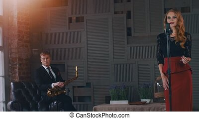 Jazz duet perform on stage of restaurant. Woman sing at microphone. Saxophonist