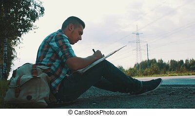 Man sit at road in countryside write on cardboard plate....