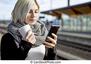 Woman With Coffee Cup Using Mobile Phone At Train Station -...