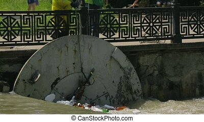 People Cleaning Polluted City River - Two men collecting...