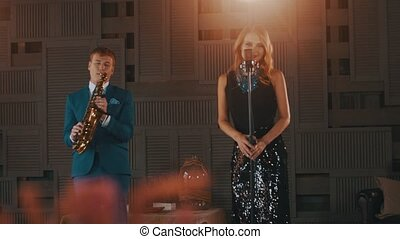 Jazz vocalist in glare dress dance sing on stage with saxophonist in blue suit