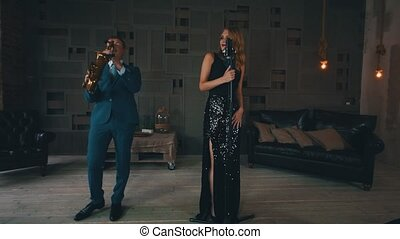 Adult jazz vocalist in glowing dress performing on stage with saxophonist. Dance