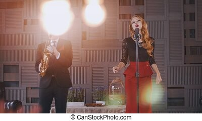 Jazz duet on stage Saxophonist Attractive vocalist sing and...