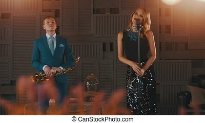 Jazz vocalist in glowing dress at microphone. Saxophonist in blue suit on stage.
