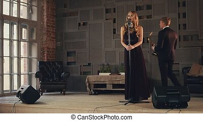 Jazz vocalist in dark dress and saxophonist in black suit perform on stage. Duet