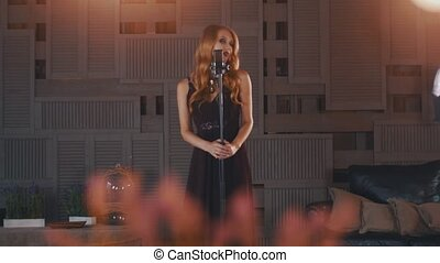 Attractive jazz vocalist in black dress perform on stage at microphone. Make up