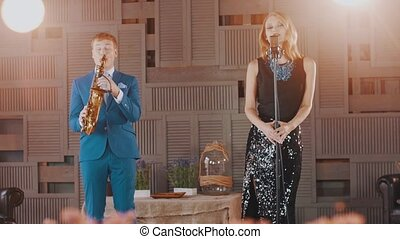 Jazz vocalist in glowing dress saxophonist in blue suit on...