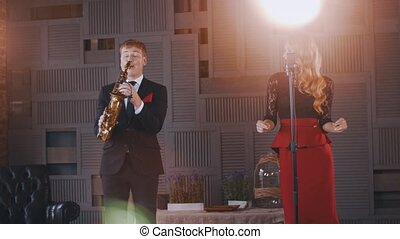 Jazz duet perform on stage. Saxophonist and vocalist. Retro...