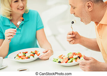 Senior married couple eating salad in restaurant - Mature...