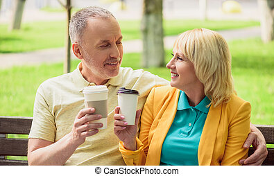 Husband and wife enjoying hot drink together - Joyful senior...