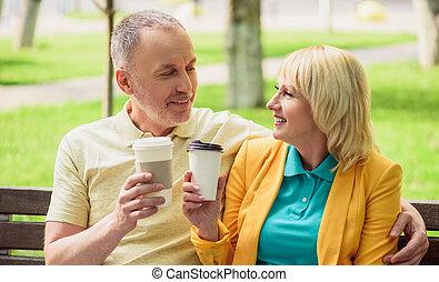 Husband and wife enjoying hot drink together - Joyful senior...