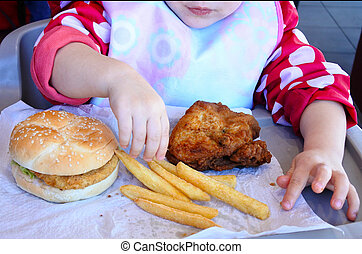 Little girl ready to eat fast food: chicken burger, French...