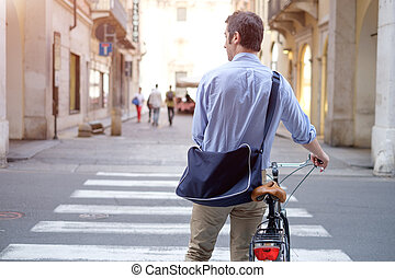 Man is standing crossing the city street with his bike