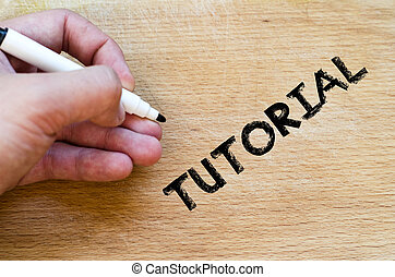 Tutorial text concept - Human hand over wooden background...