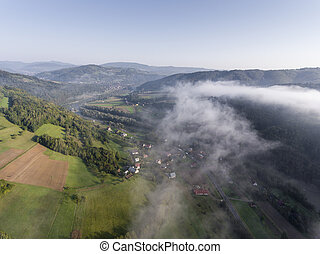 Landscape misty panorama. Fantastic dreamy sunrise on rocky mountains with view into misty valley below. Foggy clouds above forrest. View below to fairy landscape. Foggy forest hills.View from above.