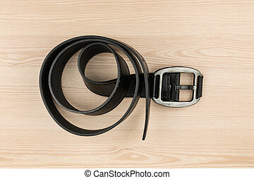 Black leather belt with buckle lying on a wooden surface,...