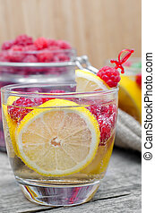 Glass of sparkling water with lemon and raspberry
