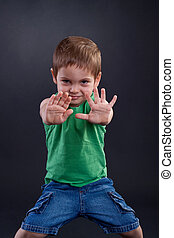 Stop signal - Child looking at camera. Stop signal with his...