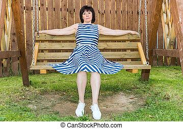 brunette woman on a wooden bench - Brunette woman in dress...