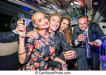 Portrait of young male and female friends with champagne flutes partying together in limousine