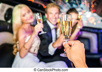 Closeup of hand toasting champagne flute with friends in...