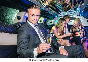 Portrait of confident young man holding champagne flute while friends discussing in limousine