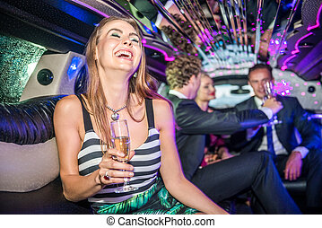 Cheerful young woman holding champagne flute while friends celebrating in limousine