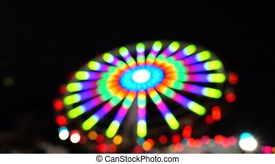 Theme park at night. Defocused spinning LED lit attraction....