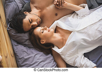 man and woman holding hands while sleeping