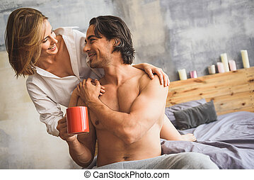 man and woman hugging in a bed - woman looking at her...
