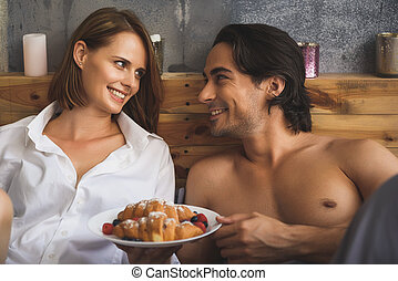 couple looking at each other while holding plate with...