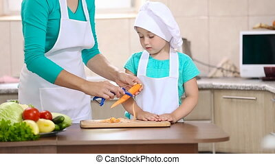 Child with mum clean carrots - Child with mum clean the...