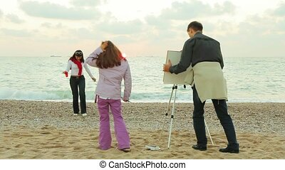 Family Draws On The Sea - Family paints on an easel in the...