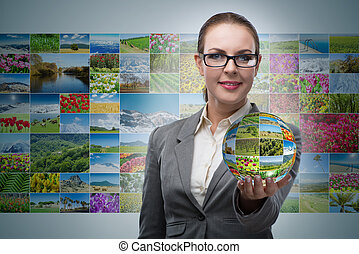 Businesswoman holding the ball with nature photos