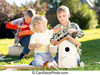 Little boys brothers building birdhouse outdoors - Three...