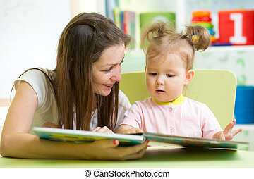 Happy mother and daughter reading a book together