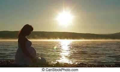 Pregnant Sits On The Lake In The Early Morning And Watch The Sunrise.