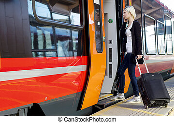 Young Woman With Wheeled Luggage Boarding Train - Full...